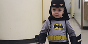 Toddler inside the museum wearing batman costume