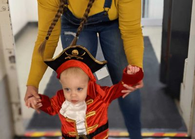 person dressed as a minion holding a toddler's hands (who is dressed as a pirate) as they walk through the Diefenbunker