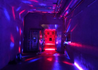 red and blue lights light up a dark hallway in the Bunker