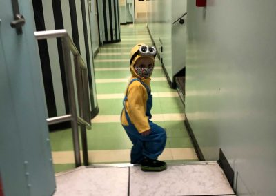 child wearing a minion costume in the hallway of the bunker