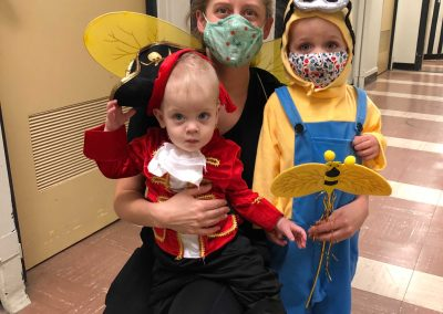 masked woman holding two children, one in a pirate costume and one in a minion costume